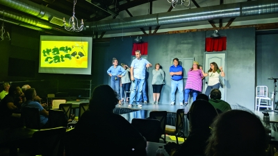 A group of improv students performing, with Charlie White front and center.